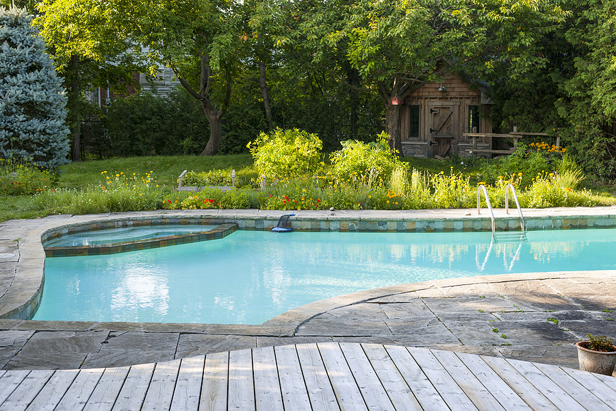 inground swimming pool with a brick and wood floor